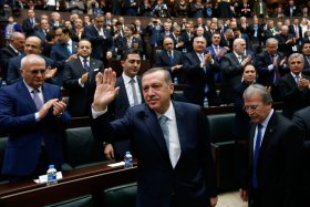 Turkey's Prime Minister Tayyip Erdogan greets his supporters as he arrives for a meeting at the Turkish parliament in Ankara Feb. 25, 2014