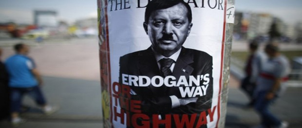 people-walk-past-poster-depicting-turkish-prime-minister-tayyip-erdogan-that-has-been-pasted-by