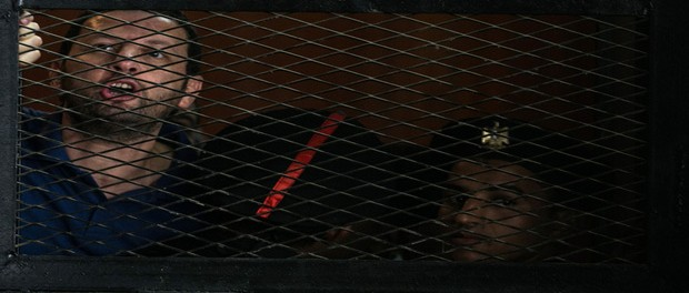 Muslim brotherhood member, Bassem al-Ouda, stands behind bars as he is tried at a court in Cairo, on August 30, 2014. An Egyptian court commuted to life imprisonment the death sentence that had been pronounced against the Egyptian Muslim Brotherhood leader, Mohamed Badie, according to state television and defence lawyers.  Four other members of the Brotherhood were sentenced to life imprisonment while six others,  tried in absentia , were sentenced to the death penalty.
