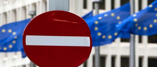 EU flags flutter in the wind behind a no-entry street sign in front of EU headquarters in Brussels on Friday, June 24.