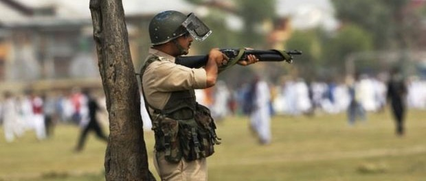 An Indian policeman aim his pellet gun at protesters during a protest in Srinagar